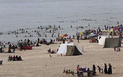 Palestinian families enjoy themselves at the Gaza City beach of the Mediterranean Sea in in the northern Gaza Strip on May 27, 2015. The region is experiencing a heat wave with temperatures reaching about 107.6 degrees Fahrenheit in the Gaza Strip. (Adel Hana/AP)