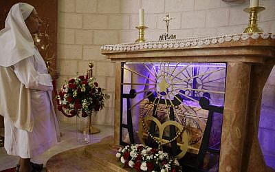 A nun stands by the tomb of Marie Alphonsine Ghattas, a nun who lived in what was Ottoman-ruled Palestine in the 19th century, at Church of the Rosary Sisters Mamilla in Jerusalem, on Saturday May 9, 2015. (Photo credit: Dusan Vranic/AP)