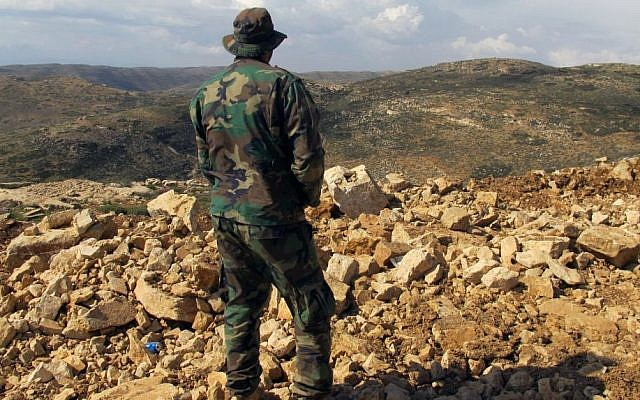 A Hezbollah fighter looks toward Syria while standing in the fields of the Lebanese border village of Brital, Lebanon, May 9, 2015. (photo credit: AP/Bassem Mroue)