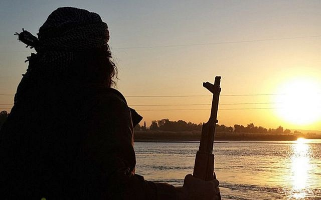 ILLUSTRATIVE: An Islamic State fighter holds his AK-47 machine gun as he stands guard on the bank of the Euphrates River in Raqqa, Syria. (Militant website via AP)