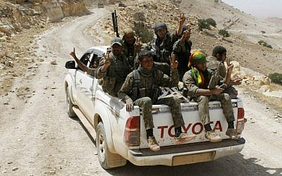 In this photo released on May 20, 2015, provided by the Kurdish fighters of the People's Protection Units (YPG), which has been authenticated based on its contents and other AP reporting, Kurdish fighters of the YPG flash victory signs as they sit on their pickup truck on their way to battle against the Islamic State group, near Kezwan mountain, northeast Syria. (The Kurdish fighters of the People's Protection Units via AP)