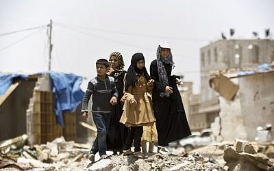 A boy and his sisters watch graffiti artists spray-paint on a wall, commemorating the victims who were killed in Saudi-led coalition airstrikes on Sana'a, Yemen, May 18, 2015. (AP/Hani Mohammed)