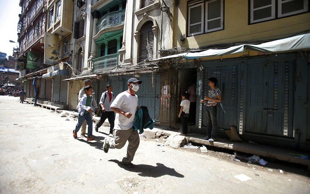 A Nepalese man runs to safety after a second earthquake hit Nepal in Kathmandu, Nepal, Tuesday, May 12, 2015 (AP Photo/Bikram Rai)