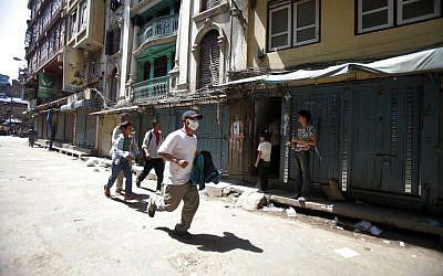 A Nepalese man runs to safety after a second earthquake hit Nepal in Kathmandu, Nepal, Tuesday, May 12, 2015 (AP Photo/Bikram Rai)