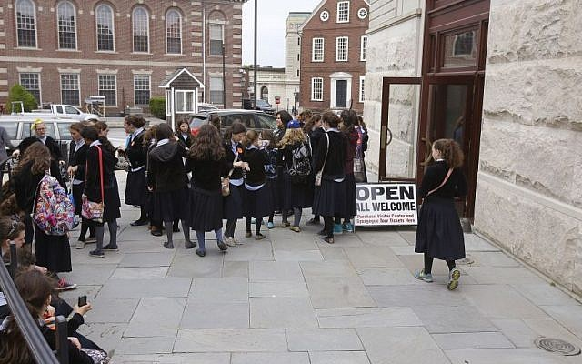 In this Thursday, May 28, 2015 photo, school girls gather outside the visitor's center at the Touro Synagogue during a tour in Newport, Rhode Island. (AP Photo/Stephan Savoia)