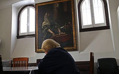In this photo taken on Tuesday, May 5, 2015, a Jewish woman reads a book at the main Jewish synagogue in Lisbon. Portugal enacted in March a law to grant citizenship to descendants of Sephardic Jews exiled during the Inquisition 500 years ago. Spain is about to adopt a similar law but its different requirements have raised criticism. (photo credit: AP Photo/Francisco Seco)
