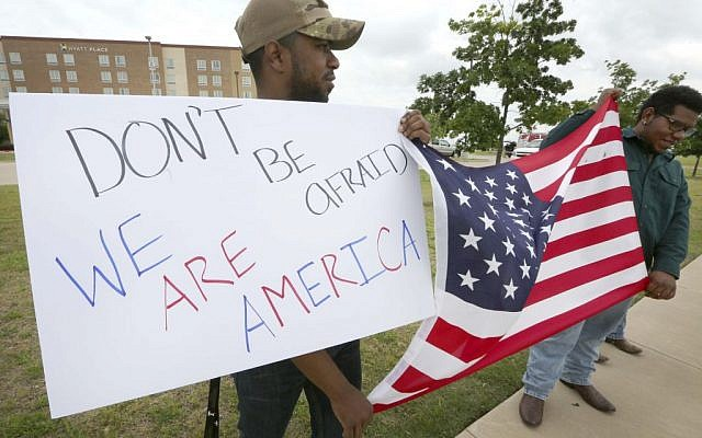 Joseph Offutt, left, and Raheem Peters hold a sign and a U.S. flag across the street from the Curtis Culwell Center, Tuesday, May 5, 2015, in Garland, Texas. A man, whose social media presence was being scrutinized by federal authorities, was one of two suspects killed in the Sunday shooting at this location that hosted a cartoon contest featuring images of the Muslim Prophet Muhammad. The Islamic State group on Tuesday claimed responsibility for the attack. (photo credit: AP/LM Otero)