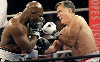 Former Republican presidential candidate Mitt Romney, right, throws punches with five-time heavyweight boxing champion Evander Holyfield at a charity fight night event Friday, May 15, 2015, in Salt Lake City (AP Photo/Rick Bowmer)