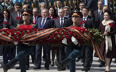 Venezuelan president's wife Cilia Flores, Venezuela's president Nicolas Maduro, Kazakh president Nursultan Nazarbayev, Russian president Vladimir Putin, Chinese president Xi Jinping and Chinese first lady Peng Liyuan attend a wreath-laying ceremony at the Tomb of the Unknown Soldier in Moscow after the Victory Parade marking the 70th anniversary of the defeat of the Nazis in World War II, in Red Square, Moscow, Russia, Saturday, May 9, 2015. At fourth left is Cuban president Raul Castro. (photo credit: AP Photo/Pavel Golovkin)