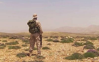 A Hezbollah fighter surveys the horizon, illustrative photo (YouTube screen capture/CNN)