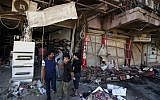 Civilians inspect the site of a bomb attack near restaurants and coffee shops filled with customers in central Baghdad's busy commercial Karradah neighborhood, Iraq, Sunday, May 3, 2015 (AP/Hadi Mizban)