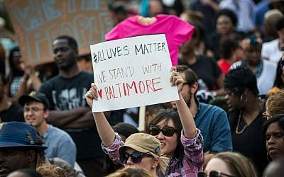 A woman holds up a sign during a rally led by faith leaders in front of Baltimore City Hall calling for justice in response to the death of Freddie Gray, May 3, 2015 in Baltimore, Maryland. (Andrew Burton/Getty Images/via JTA)