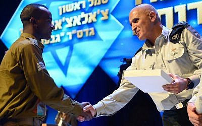 Sergeant Chalachew Mekonen receives a citation for service during Operation Protective Edge from Southern Command chief Sami Turgeman in February 2015. (IDF Spokesperson's Unit)