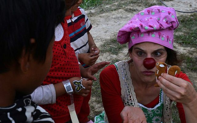 An Israeli medical clown entertains a Nepalese earthquake victim during a visit to a makeshift army camp in Kathmandu on May 6, 2015 (photo credit: AFP/PRAKASH MATHEMA)