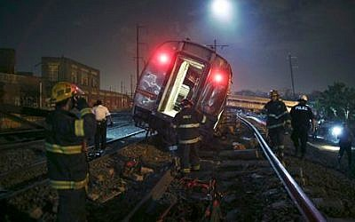 Emergency personnel work the scene of a deadly train wreck, Tuesday, May 12, 2015, in Philadelphia. (photo credit: AP/Joseph Kaczmarek)