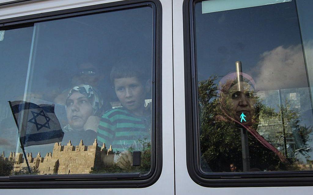 Arab women watch Jerusalem Day celebrations through their bus window, May 20, 2012 (Nati Shohat/Flash90)