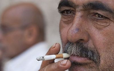 A Palestinian man smokes a cigarette in the alleys of Jerusalem's Old City, on June 12, 2013. (Neal Badache/Flash90)