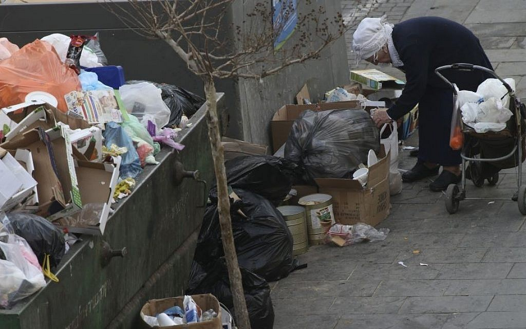 An Israeli woman searches for objects in a garbage container in Jerusalem, April 2, 2015 (photo by Nati Shohat/Flash90)