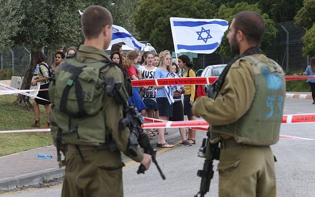 Israeli soldiers stand in front of Jewish youth demonstrating with Israeli flags, at the scene of a drive-by attack near Alon Shvut, Gush Etzion, on May 14, 2015. Nati Shohat/Flash90