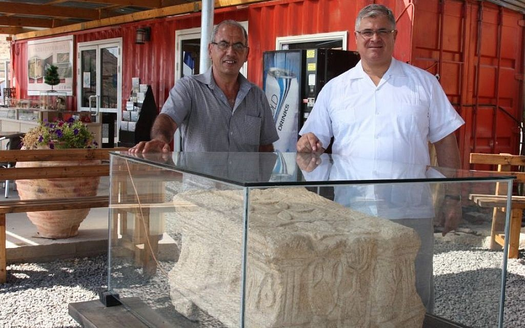 Father Juan (right) and archaeologist Arfan Najjar with the altar stone at Magdala (Shmuel Bar-Am)