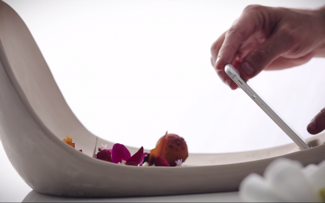 One of ceramic designer Adi Nissani's special creations for 'Foodography,' a plate designed to simultaneously  hold a cellphone and provide a clean backdrop for a diner's meal. (Screen capture: YouTube)