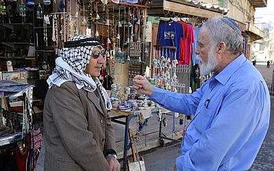 A Palestinian and a Jew seen talking outside a shop near the Cave of the Patriarchs in Hebron, on December 10, 2014. (Gershon Elinson/Flash90)