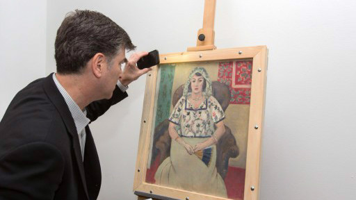 "This handout photo released by Art Recovery shows Christopher Marinello, lawyer representing the heirs of Paul Rosenberg, looking at Henri Matisse's 'Femme Assise' (""Seated Woman"") painting on May 15, 2015 in Munich, Germany (AFP PHOTO / ART RECOVERY / WOLF HEIDER-SAWALL)"