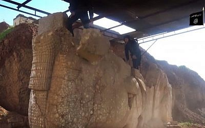 In this image made from video posted on a social media account affiliated with the Islamic State group on Thursday, Feb. 26, 2015, militants destroy winged-bull Assyrian protective deity in the Ninevah Museum in Mosul, Iraq. (Photo credit: (AP via militant social media account, File)