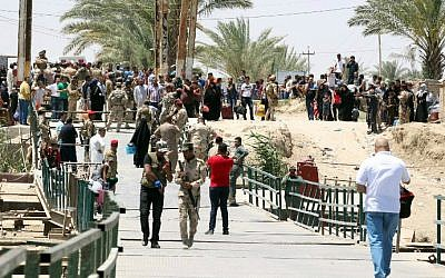 Residents from the city of Ramadi, who fled their homes on May 16, 2015 as Islamic State (IS) group militants tightened their siege on the last government positions in the capital of Anbar province, a day after they seized the city's government headquarters, wait to cross Bzeibez bridge, on the southwestern frontier of Baghdad with Anbar province, after IS group jihadists took control of all the other routes connecting the province with the Iraqi capital. Taking control of Ramadi would constitute the group's most important victory this year in Iraq, and would give the jihadists control of the capitals of two of its largest provinces. AFP PHOTO/SABAH ARAR