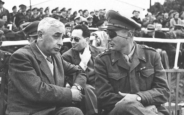 Defense Minister Pinchas Lavon, left, and IDF Chief of the General Staff Moshe Dayan, with Shimon Peres in the background, on February 8, 1953 (photo credit: GPO/ courtesy of IDF Archive in the Defense Ministry)