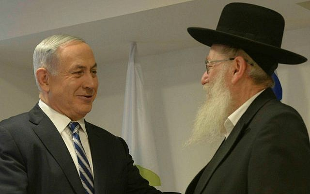 Prime Minister Benjamin Netanyahu (L) congratulates then-incoming Deputy Health Minister Yaakov Litzman at the Health Ministry in Jerusalem on May 20, 2015. (Amos Ben Gershom/GPO/Flash90)