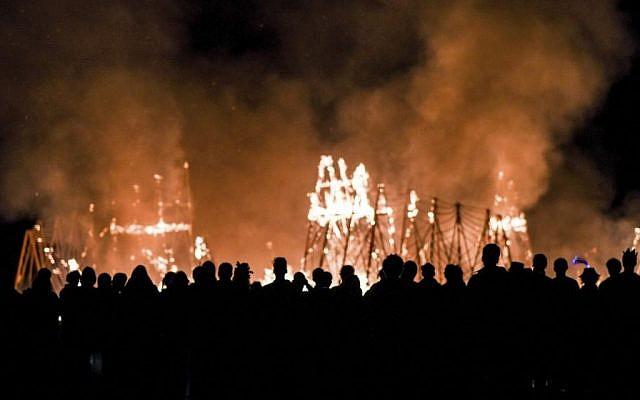 Revelers watch the wood installations burn at the second annual Midburn festival, the Israeli version of Burning Man, on May 24, 2015. (Ben Kelmer/Flash90)