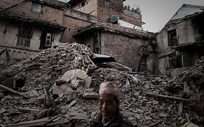 A pedestrian walks past destroyed houses in the village of Satungal on the outskirts of Kathmandu on May 5, 2015, following a 7.8 magnitude earthquake which struck the Himalayan nation of Nepal on April 25 (photo credit: AFP/Philippe Lopez)
