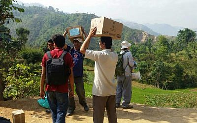 Nepalese aid workers carrying supplies they received from Israel (photo credit: Tevel b'Tzedek)