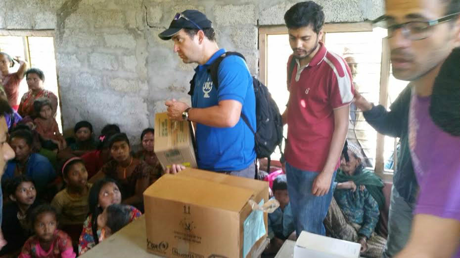Volunteers distribute supplies to a Nepalese crowd (photo credit: Tevel b'Tzedek)