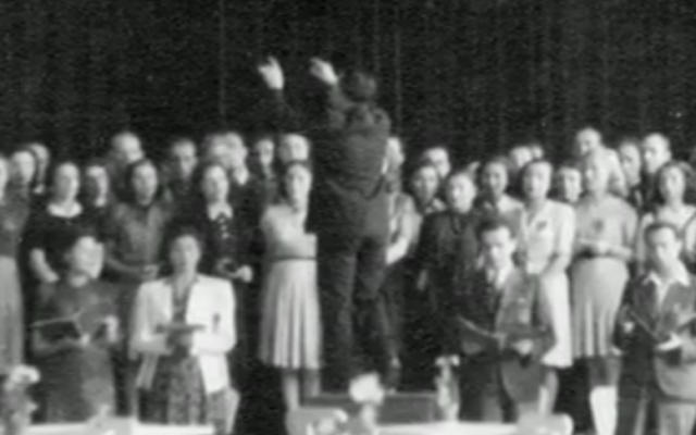 """The only known photo of Theresienstadt inmates performing Verdi's Requiem for the Dead, taken during the final performance on June 23, 1944. Raphael """"Rafi"""" Schachter  is seen conducting the choir, with Adolf Eichmann and an International Red Cross delegation in the audience (courtesy: The Terezin Foundation)"""