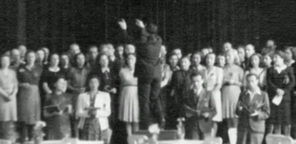 The only known photo of Theresienstadt inmates performing Verdi's Requiem Mass, taken during the final performance on June 23, 1944. Raphael 'Rafi' Schachter is seen conducting the choir, with Adolf Eichmann and an International Red Cross delegation in the audience (courtesy: The Terezin Foundation)