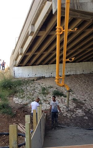 The cement truck poured the CLSM through the chute, over the site of the overpass, into the crevice under the bridge (Jessica Steinberg/Times of Israel)