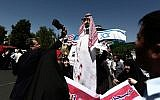 An Iranian man beats with his shoe an effigy of a Saudi royal with flags of the United States and Israel attached to it during a demonstration in Tehran on May 8, 2015. (photo credit: AFP/Behrouz Mehri)