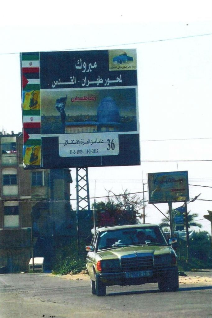 A car drives past a Shiite organization's poster in Gaza, which reads, 'Congratulations to the Iran-Jerusalem axis,' 'Palestine tomorrow' and '36 years of Pride and Independence.'