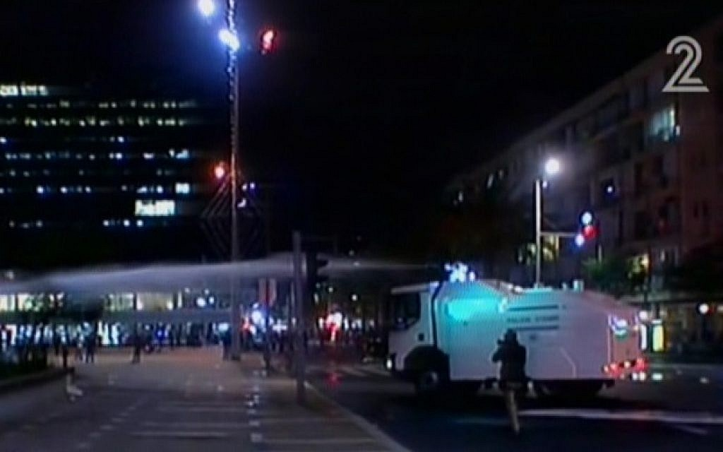 "A truck spraying so-called ""skunk water"" at protesters to break up a rally in Tel Aviv on May 3, 2015. (screen capture: Channel 2)"