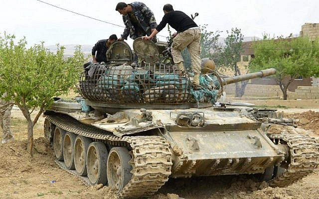 Syrian regime forces check a tank on May 9, 2015 in Assal al-Ward, a small regime-controlled village situated on the mountain of al-Kanissa in the Qalamun region, after they seized control of several hilltops in the mountainous area that straddles the Syria-Lebanon border with the support of Lebanon's Shiite Hezbollah movement. (photo credit: AFP/STR)