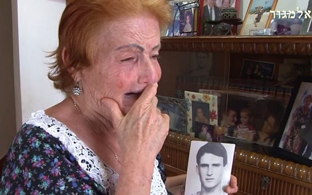 The mother of Moshe Tamam holds an image of her soldier son, who was murdered by a group of Arab Israelis in 1984 (screen capture: YouTube)