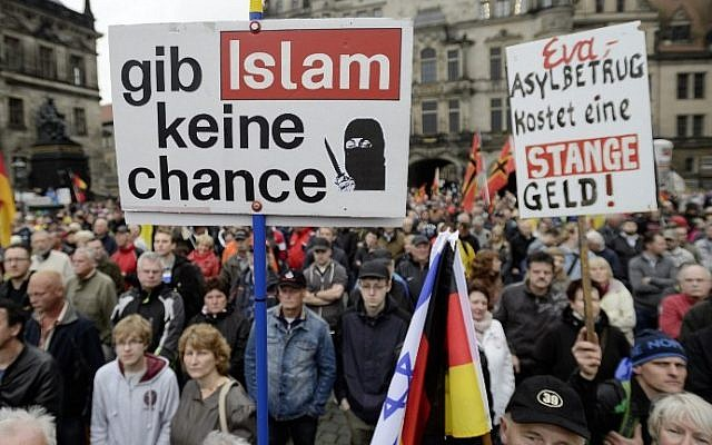 """Supporters of the German right-wing movement PEGIDA (Patriotic Europeans Against the Islamisation of the Occident) hold up a poster reading """"Give No Chance to Islam"""" as they attend a PEGIDA rally on June 1, 2015 in Dresden, eastern Germany (Jens Schlueter/AFP)"""
