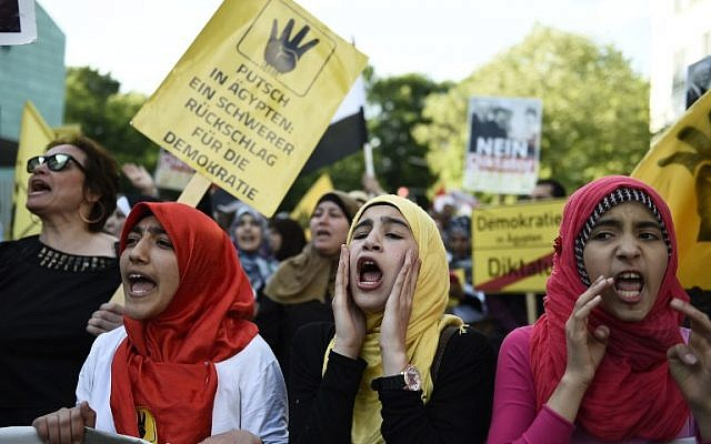 "Young women wearing headscarves hold up a poster reading ""Coup in Egypt - Severe Setback for Democracy"" as they take part in a demonstration against the policy of the Egyptian President on June 3, 2015 near the Egyptian Embassy in Berlin. (AFP PHOTO / ODD ANDERSEN)"