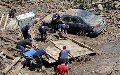 Rescuers and local residents collect debris at a flooded area in the Georgian capital Tbilisi on June 15, 2015. (Vano Shlamov/AFP)