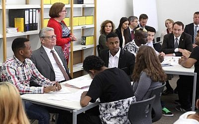 Iluustrative photo: German President Joachim Gauck (C) meets young refugees during his visit at the Friedrich-Feld vocational school of commerce in Giessen, central Germany, on June 17, 2015. (Daniel Roland/AFP)