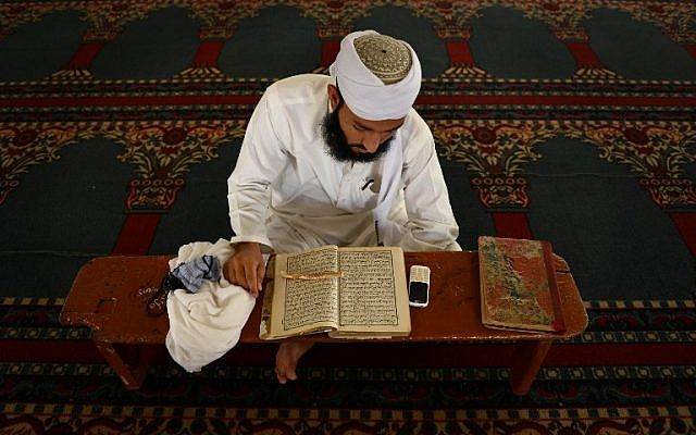 A Pakistani Muslim man recites the Quran at a mosque ahead of Ramadan in Peshawar on June 18, 2015. AFP PHOTO/ A MAJEED