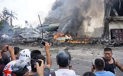 An Indonesian military transport plane crashed on June 30 shortly after taking off and exploded in a ball of flames in a residential area,  June 30, 2015.  (AFP / MUHAMMAD ZULFAN DALIMUNTHE)