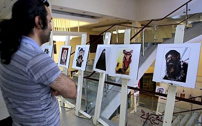 An Iranian man looks at cartoons displayed during an exhibition as part of the Daesh (Islamic State jihadist group) International Cartoon and Caricature Contest on May 31, 2015 at the Arasbaran gallery in Tehran. (AFP PHOTO / ATTA KENARE)